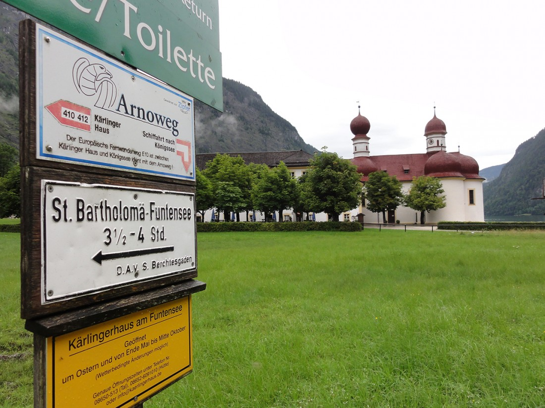 Arnoweg: Die Kirche von St. Bartholomä am Königssee mit Wegweiser